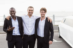 Handsome men posing next to a limousine Stock Photo