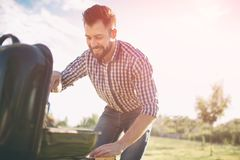 Handsome man preparing barbecue for friends. man cooking meat on barbecue - Chef putting some sausages and pepperoni on. Handsome men preparing barbecue for royalty free stock photos