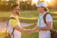 Men playing golf. Handsome men are shaking hands and smiling when meeting on a golf course Royalty Free Stock Images