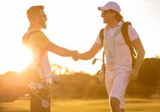 Men playing golf. Handsome men are shaking hands and smiling when meeting on a golf course Stock Images