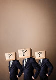 Handsome men in suit gesturing with drawn question marks on box Royalty Free Stock Photography