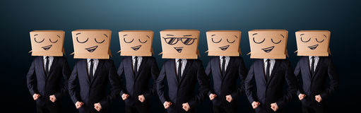 Handsome men in suit gesturing with drawn smiley faces on box Royalty Free Stock Photos