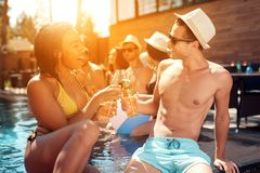 Handsome man in summer hat and beautiful woman cheering with beer bottles in swimming pool. Royalty Free Stock Images