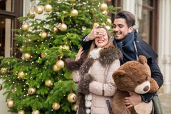 Handsome man surprising his girlfirend witha christmas teddy bea