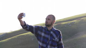 Handsome men taking selfie photo with mobile phone at the mountain landscape stock video footage