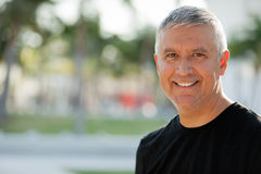 Handsome middle age man. Handsome unshaven middle man wearing a black t shirt in an outdoor setting Royalty Free Stock Photo