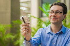 Handsome middle aged businessman is paying with a credit card for business lunch at the restaurant Stock Images