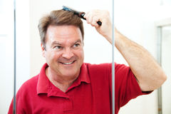 Handsome Mature Man Brushes His Hair. Handsome middle-aged man brushing his hair, looking in the bathroom mirror Stock Photo