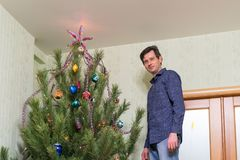 Handsome middle-aged man decorates a Christmas tree with new yea