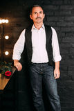 Handsome middle aged man is dressed in a white shirt and a black vest, holding a red rose flower, bachelor. Black background. Stock Photo