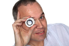 Handsome middle aged man holding lens to eye Stock Image