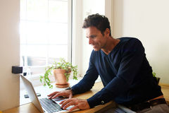 Handsome middle aged man with laptop at home Royalty Free Stock Photo