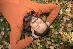 Handsome middle-aged man lying on the autumn leaves in park Royalty Free Stock Photography