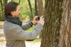Handsome middle-aged man making photos in the park Stock Photo