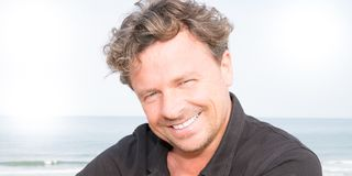 Handsome middle-aged man smiling. At the beach Stock Images
