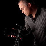 Handsome middle aged man taking a photo. Middle aged man taking a photograph with a digital SLR camera in the dark with black background Royalty Free Stock Image