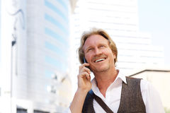 Handsome middle aged man talking on mobile phone in city. Close up portrait of handsome middle aged man talking on mobile phone in city Stock Photos