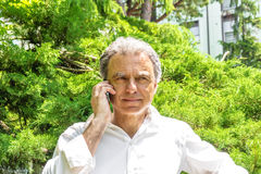 Handsome middle-aged man talking on mobile phone Royalty Free Stock Image