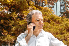 Handsome middle-aged man talking on mobile phone. Handsome middle-aged man with salt pepper hair dressed with white shirt is talking on mobile phone in city park Stock Photography
