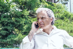 Handsome middle-aged man talking on mobile phone. Handsome middle-aged man with salt pepper hair dressed with white shirt is talking on mobile phone in city park Royalty Free Stock Photo