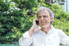 Handsome middle-aged man talking on mobile phone. Handsome middle-aged man with salt pepper hair dressed with white shirt is talking on mobile phone in city park Stock Photo