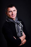 Handsome middle aged man wearing a scarf. On black Stock Photography