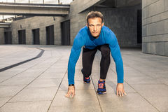 Handsome middle aged serious man in blue black sports uniform and headphones and fitness tracker is running in the city. Royalty Free Stock Photography