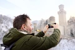 Handsome milddle age man making photo of famous royal castle Neuschwanstein Stock Photo