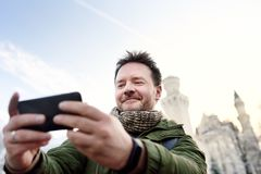 Handsome milddle age man making a self portrait selfie with famous royal castle Neuschwanstein on background Stock Photo
