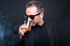 Handsome millionaire enjoying a glass of whiskey. On dark background Royalty Free Stock Photography