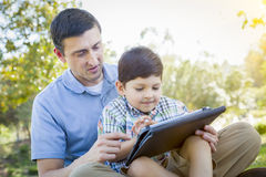 Handsome Mixed Race Father and Son Playing on Computer Tablet Royalty Free Stock Image