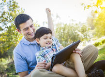 Handsome Mixed Race Father and Son Playing on Computer Tablet Stock Photo