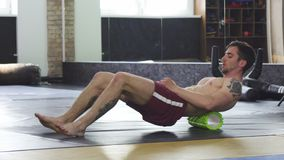 Athletic muscular man relaxing after training, using foam roller stock video footage