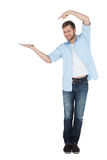 Handsome model holding laptop and pointing at it Stock Photo