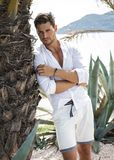 Handsome model under palm tree stock photos