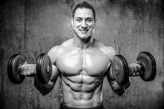 Handsome model young man training arms in gym Royalty Free Stock Photo