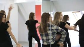 Handsome models in black uniform dance in ballroom looking in mirror. stock footage