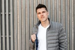 Handsome modern young man with a stylish hairstyle in a fashionable gray jacket in a trendy white T-shirt poses. Near a vintage wooden wall of boards stock image