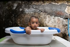 An handsome 7-month-old boy is bathing in his bathtub with an old but artistic background royalty free stock images