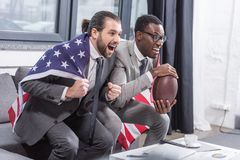 handsome multiethnic men in suits with american flag on shoulders watching american football match