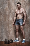 Handsome muscle man with dumbbells on wall background Stock Images