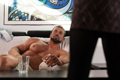 Handsome muscle man hangover in bed looking on woman front Royalty Free Stock Photo