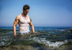 Handsome muscle man in the sea with wet shirt on Royalty Free Stock Photos
