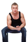 Handsome muscle man sitting on chair Royalty Free Stock Photos