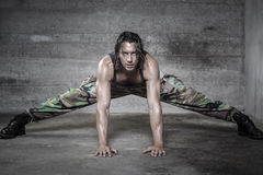 Handsome muscle man wears camouflage pants. Handsome muscle man stretches his muscle looking at camera Stock Photo