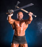Handsome muscular ancient warrior with axe and sword Stock Images
