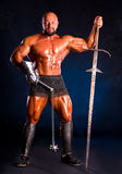 Handsome muscular ancient warrior with a sword and mace Stock Image