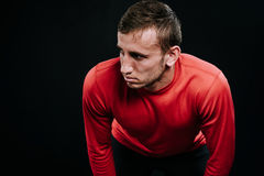 Handsome muscular athlete taking break standing against dark background. Tired young Caucasian runner resting after hard training. Stock Photo
