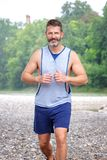 Handsome muscular bearded athlete running outdoors Stock Images