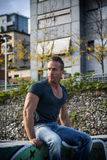 Handsome muscular blond man sitting in city setting Royalty Free Stock Images